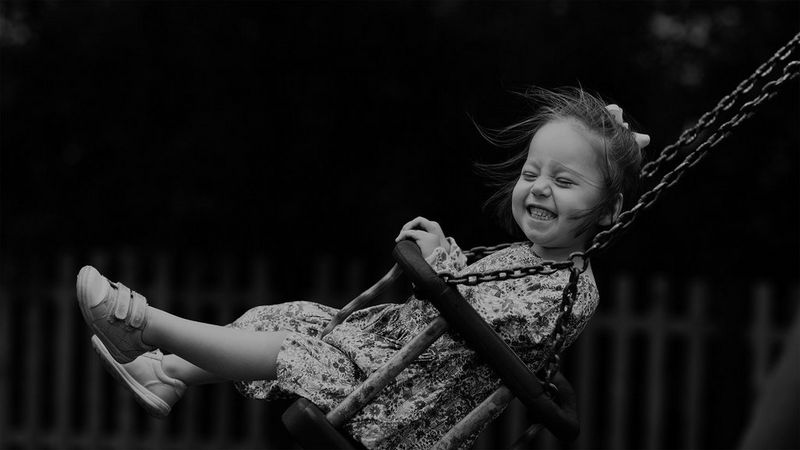 A smiling child playing on a swing.
